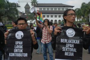 Sejumlah wartawan membawa poster saat aksi hari buruh di Bandung, Jawa Barat, Jumat (1/5). Sejumlah pekerja media massa dan Aliansi Jurnalis Independen Bandung ikut menggelar aksi menuntut perusahaan media untuk menetapan upah sektoral, jaminan asuransi, penetapan kontrak yang jelas untuk kontributor, dan meningkatkan kesejahteraan jurnalis di era konvergensi media. TEMPO/Prima Mulia